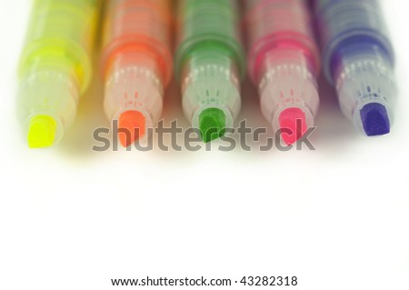 Close up of colorful highlighters lined up isolated on white