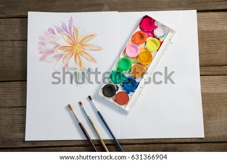 Close-up of colorful palette, paintbrushes and paper on wooden surface