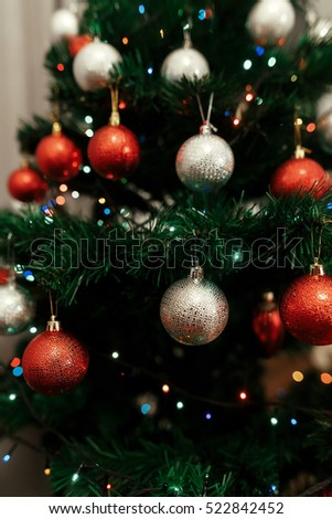 Close-up of colorful, red and silver christmas ornaments on christmas tree with lights, holiday greeting card concept  - Shutterstock ID 522842452