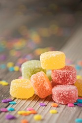 Close-up of colorful round gummy candies on wooden background and confetti. Jelly beans, jelly sweets.