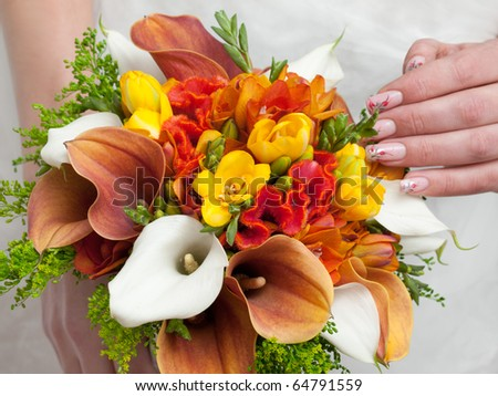 close-up of colorful wedding bouquet at bride\'s hands