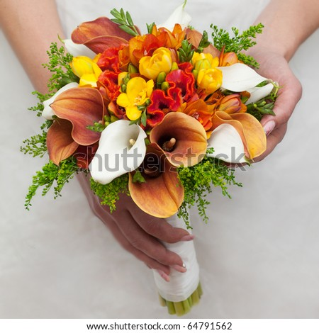 close-up of colorful wedding bouquet at bride's hands