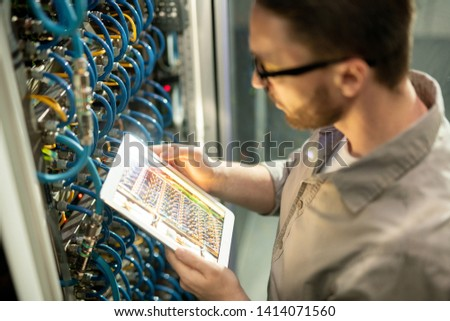 Close-up of concentrated man in shirt standing by mainframe and using digital tablet to check connectivity in datacenter room #1414071560