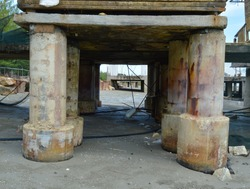 Close up of concrete poles, pillar of the fish bridge. Under the old bridge, pier fishing boat or jetty covered with small shell stick on bridge pillars