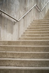 Close up of concrete staircase with metal hand rail