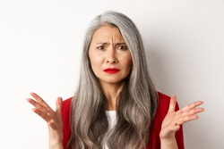 Close up of confused asian female manager with grey hair, wearing red blazer and makeup, spread hands sideways and staring puzzled at camera, white background