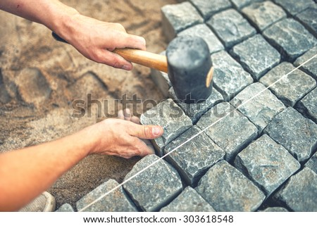 Close-up of construction worker installing and laying pavement stones on terrace, road or sidewalk. Worker using stones and rubber hammer to build stone sidewalk #303618548