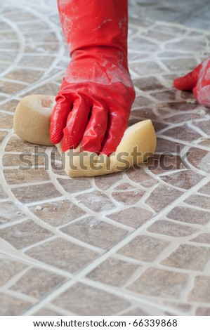 Close up of construction worker installing decorative tiles