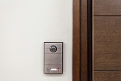 Close up of contemporary doorbell near door with security panel, intercom and video camera in modern house against white copy space wall