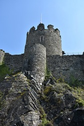 close up of Conwy castle stone tower turrets.  Conwy's fortress towering high in the blue sky on a sunny spring day