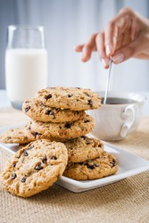close up of cookie and hand stirring cup of tea/coffee
