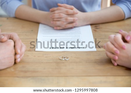 Close up of couple getting divorced in lawyers office with decree paper legal document and wedding rings on table, family separation, marriage dissolution, divorce mediation and settlement concept #1295997808