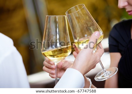 Close-up of couple hands holding champagne flutes during celebration