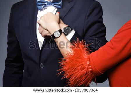 Close-up of couple hands. Well dressed stylish man and woman wearing wristwatches.