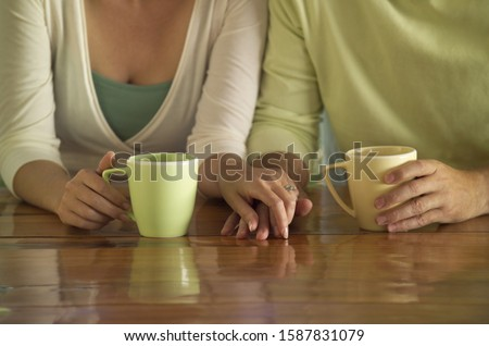 Photo of Close up of couple holding hands with coffee