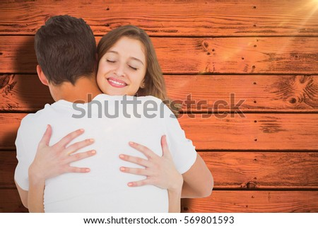 Close up of couple hugging against pink paint splashed surface #569801593