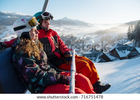 Close-up of couple man and woman snowboarders on a cable ski lift in the morning in Bukovel enjoying a beautiful view of the Carpathian Mountains copyspace recreation active sport seasonal concept #716751478