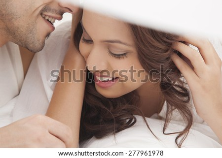 Close-up of couple romancing in bed