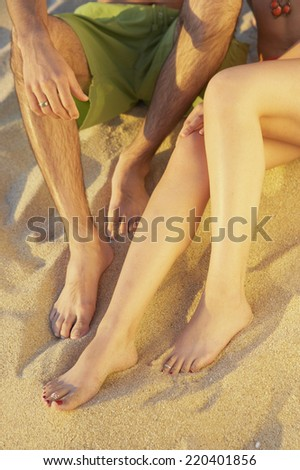 Close up of couple's legs on the beach #220401856