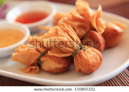 Close up of crab rangoon with sauce