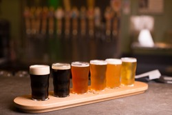 Close up of craft beer tasting flight at local brewery of small pint glasses in a row on a tray with rainbow variety of dark malt stouts to golden yellow hoppy ales on bar, with taps in background