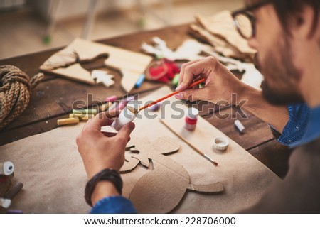 Close-up of craftsman painting xmas symbols with white gouache Сток-фото ©