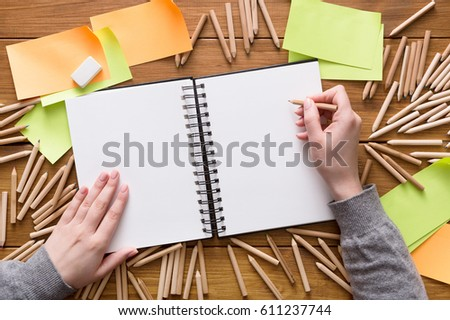 Close-up of creative designer drawing something in sketchbook at workplace. Top view flat lay shot of many blank sticky notes, color pencils on wooden table background, copy space, nobody, objects #611237744