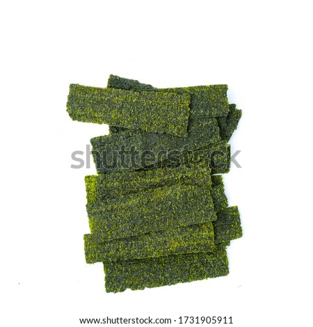 Photo of  Close-up of Crispy dried seaweed, Nori chips piece of roasted seaweed sheet isolated on white background, macro or close-up Healthy food concept, flat lay roasted seaweed