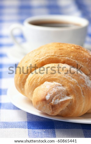 Close-up of croissant in white plate and white cup of black coffee on blue checkered tablecloth.
