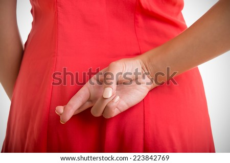 Close up of crossed fingers behind a woman's back ストックフォト ©