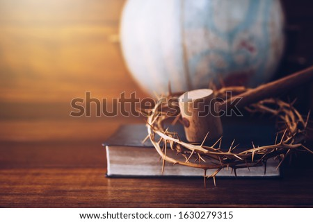 Close up of crown of thorns of Jesus and wooden hammer look like Judge gavel on  bible over Blurred world globe  on wooden table. Christian background show God justice and Christ's redemption  concept