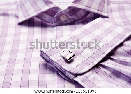 Close-up of cuff link on men's checkered shirt