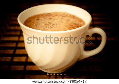 Close-up of cup of coffee with foam in the dark