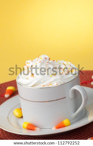 Close up of cup of fresh, delicious Pumpkin Spice Coffee, and candy corn