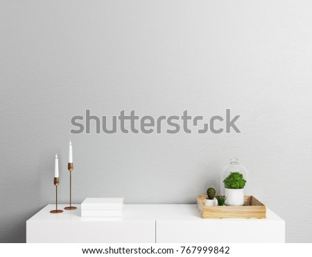Close up of cupboard top with candles, green plants, books, other decorative items and copy space on empty wall. Design, decoration and advertising concept. Mock up, 3D Rendering
