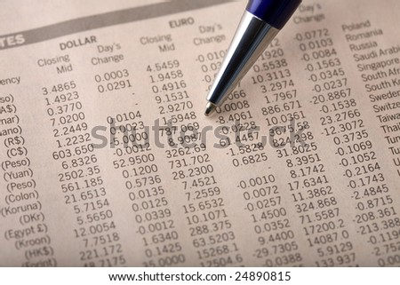 Close-up of currency exchange rate section of a financial newspaper, with pen pointing at forex rates