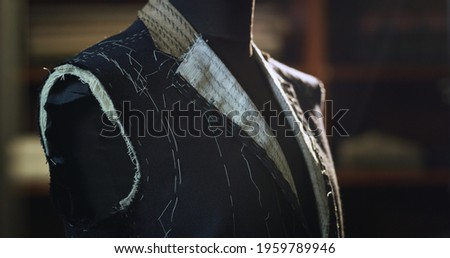 Close up of custom made high quality tailored suit by designer on tailor mannequin in luxury tailoring atelier.  Concept of fashion, handmade, hand craft, couturier and business. Stockfoto ©