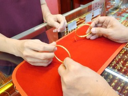 Close up of customer is checking bracelet before sell or buy at gold/pawn shop.