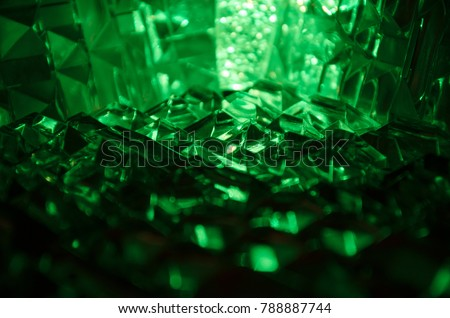 Close up of cut crystal in mysterious emerald light.Magic shiny background.Abstract.