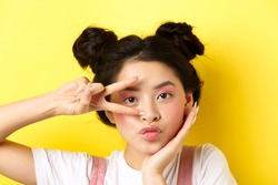 Close-up of cute asian woman with bright glamour makeup, long fingernails, showing v-sign and pouting silly at camera, standing kawaii on yellow background