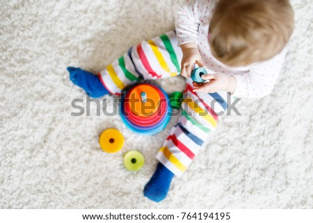 Close-up of cute beautiful little baby girl playing with educational toys at home or nursery. Happy healthy child having fun with colorful wooden rainboy toy pyramid. Kid learning different skills #764194195