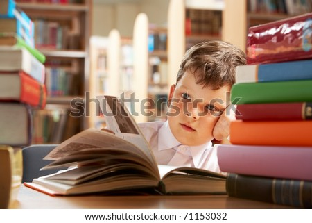 Close-up of cute boy reading book while preparing for lesson in library