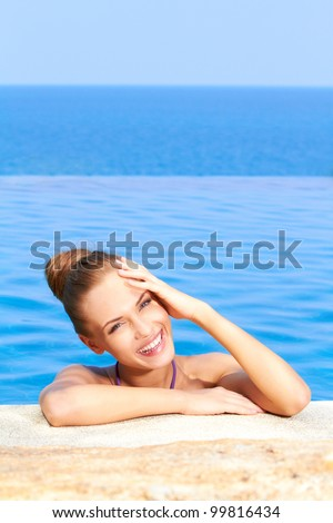 Close up of cute girl in infinity pool with copy space