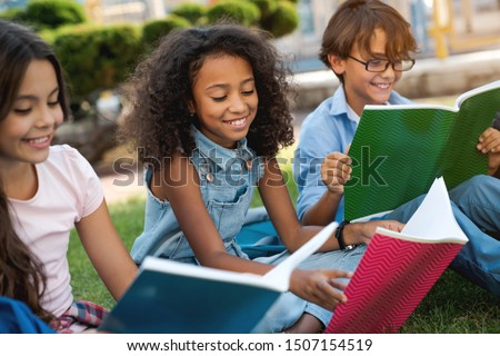 Close up of cute happy little school children with backpacks and notebooks sitting at the grass park outdoors #1507154519