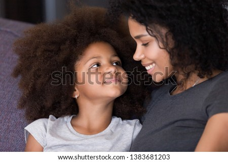 Close up of cute little African American girl looking at young mom cuddling together on couch at home, black mother and daughter hug showing love and affection, mommy embrace kid as best friend