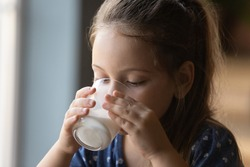 Close up of cute little Caucasian 6s girl kid drink tasty organic wholegrain milk with vitamins calcium from glass. Small child enjoy delicious nutritious lactose free yoghurt. Healthcare concept.