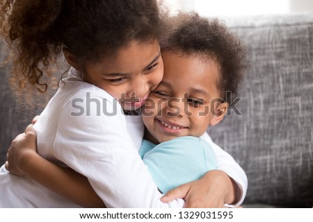 Close up of cute mixed race little boy and girl hug sitting on couch, making peace after fight, funny small African American brother and sister embrace show love and support. Best friends concept