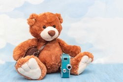 Close-up of cute plush teddy bear toy on pastel sky background. Stuffed toy with old vintage photocamera. Concept of photography, rarity and studio shooting concept, copy space