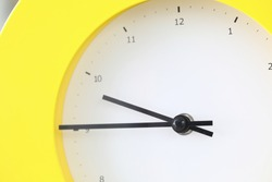 Close-up of cute round shaped bright yellow clock with black arrows. Office timepiece. Hour minute second. Interesting design. Running time and opportunities concept
