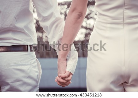 Close up of cute young newlyweds holding their hands  #430451218